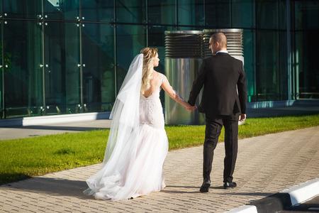 adorabili sposi il giorno del loro matrimonio camminando lungo la passerella vicino al moderno edificio contemporaneo Archivio Fotografico