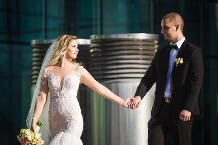 splendida sposa che tiene lo sposo il giorno del loro matrimonio camminando lungo la passerella vicino al moderno edificio contemporaneo