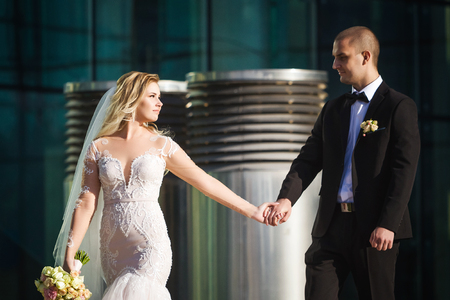 stunning bride keeping groom on their wedding day walking along the walkway near the modern contemporary building