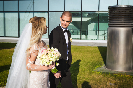 Happy bride and groom on their wedding day walking along the walkway near the modern contemporary building looking at each other