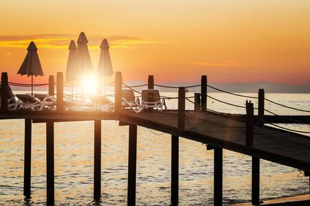 stunning view of the pier with umbrellas and deck chairs on beautiful sunset. sky is red and orange, the sea is calm. holiday concept