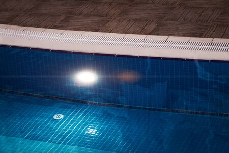 tiled edge of clean and clear swimming pool with blue mosaic. underwater lamp lightening the basin at night Stock Photo