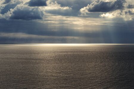 Calm seascape with beautiful cloudy sky where sun rays are getting through the clouds on the sea