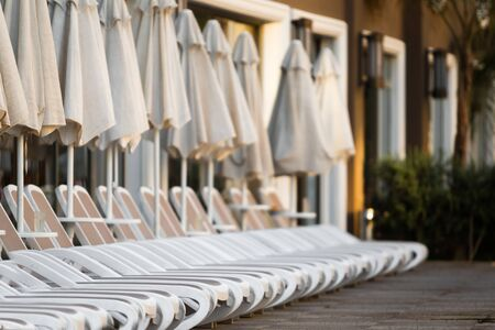 Row of white plastic deck chairs with umbrellas near the swimming pool . hotel exterior