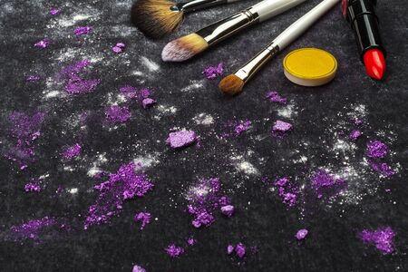 three different brushes, lipstick and purple loose eye shadows lying on a black background. concept of professional make up artist tools. free space for text Stok Fotoğraf
