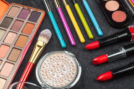 set of various cosmetics including lipstick, palette, powder, mascara, brushes and perfumes. concept of professional makeup