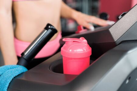 close up towel and a shaker standing on the treadmill in the gym. girl is running on the background. Concept of cardio exercises and healthy way of life
