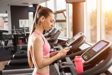 slim beautiful girl with a ponytale standing on the running track in the gym holding a phone wearing earphones listening to music. Concept of cardio exercises and healthy way of life
