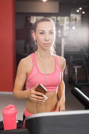 slim beautiful woman with a ponytale running on the treadmill in the gym with a phone wearing earphones listening to music. Concept of cardio exercises and healthy way of life