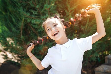 happy cute small girl wearing white shirt having fun holding her braids in a sunny summer park. pine trees on a background