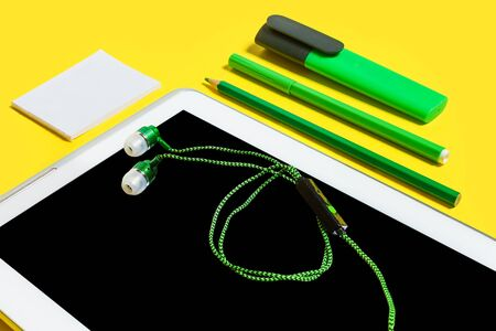 row of business or education accessories close up. green pencils, paper stickers, markers and earphones lying on a tablet pc on a yellow surface. concept of the office gadgets