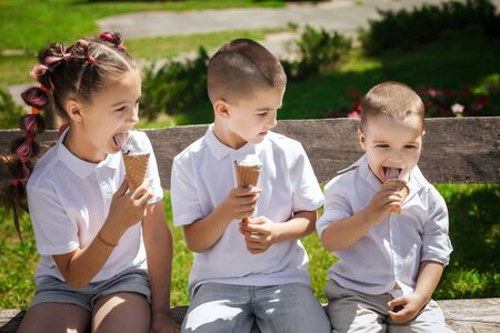 three adorable cute kids eating ice cream sitting on a wooden bench in the park. fun holiday concept Imagens