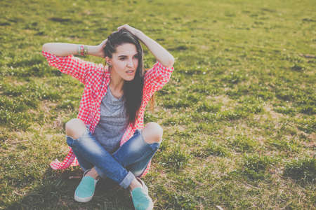 cute hipster woman sitting on the meadow. Looking at camera. Positive human emotion facial expression body language, concept of funny girl. Dressed in a gray t-shirt, and a shirt in a red cage Stock fotó