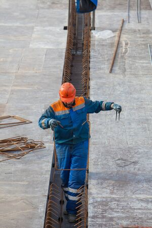 fixer: Construction Worker fixes reinforcement on site Stock Photo