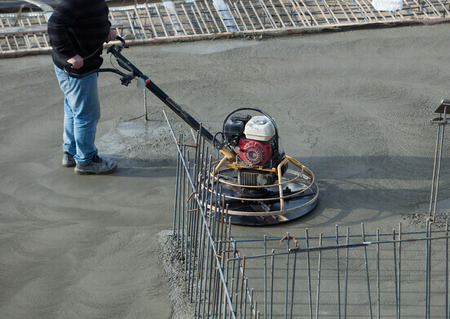 grout: Construction worker produces the grout and finish wet concrete with a special tool. Float blades. For smoothing and polishing concrete, concrete floors.