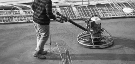 finishing: Construction worker produces the grout and finish wet concrete with a special tool. Float blades. For smoothing and polishing concrete, concrete floors.