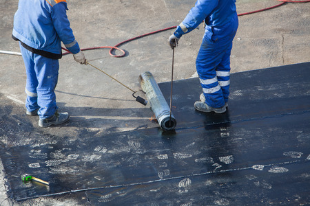 Professional installation of waterproofing on the concrete foundation. Two worker at construction site