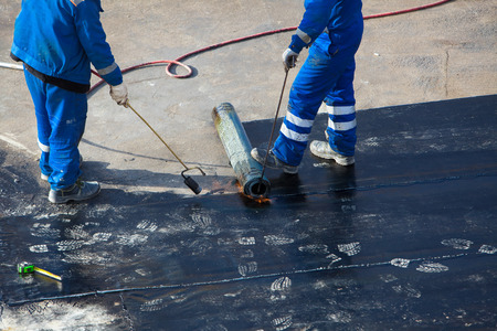 waterproofing material: Professional installation of waterproofing on the concrete foundation. Two worker at construction site