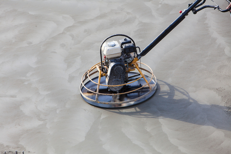 Construction worker produces the grout and finish wet concrete with a special tool. Float blades. For smoothing and polishing concrete, concrete floors.
