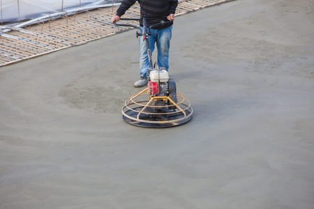 floor machine: Construction worker produces the grout and finish wet concrete with a special tool. Float blades. For smoothing and polishing concrete, concrete floors.