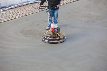 concrete: trabajador de la construcción produce la lechada y acabado de hormigón húmedo con una herramienta especial. Flotar cuchillas. Para alisar y pulir hormigón, suelos de hormigón.