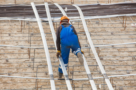 on rebar: Construction Worker connects rebar at a construction site