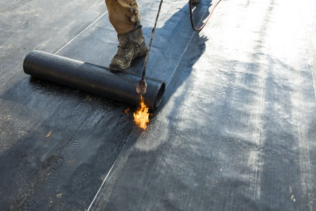 waterproofing material: waterproofing roll bituminous material in the trench. construction worker manufacturer uses a gas burner propane tank fire.