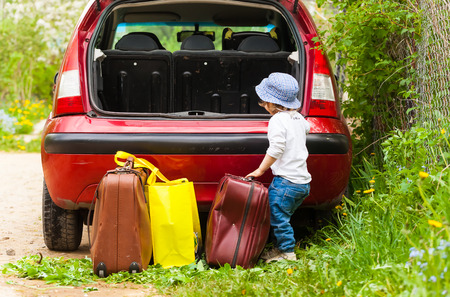 The kid puts the suitcase in the car