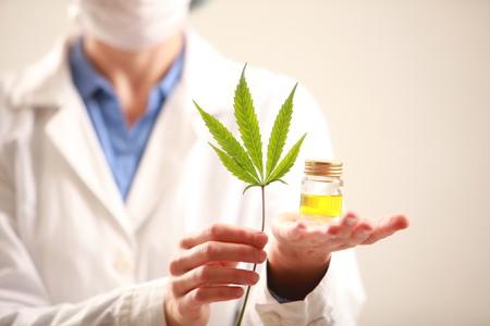 Vrouw arts die een cannabis blad en oil.alternative geneeskunde