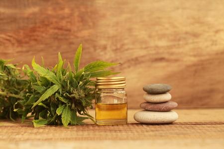 Grünblätter des medizinischen Hanfs mit Extraktöl auf einem Holztisch. alternative Medizin