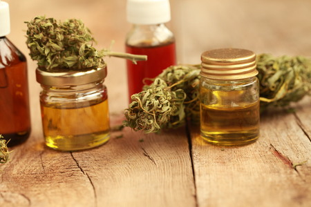 Green leaves of medicinal cannabis with extract oil on a wooden table. alternative medicine