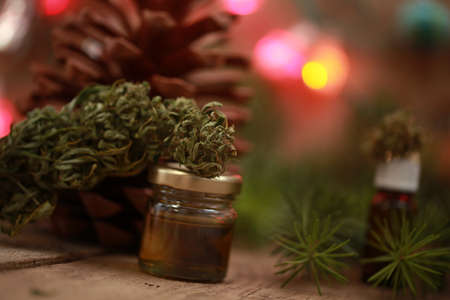 Cannabis oil in a bottle and hemp on a christmas background