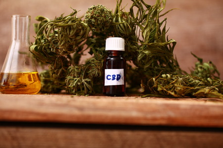 Green leaves of medicinal cannabis with extract oil on a wooden table Stock Photo