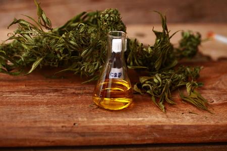 木製のテーブルの抽出油と薬用大麻の緑の葉 写真素材