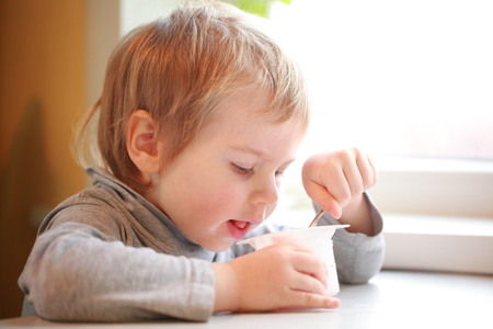 the child eats yogurt with a spoon sitting at the table Stock Photo