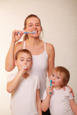 family mom and two blond boys brush their teeth