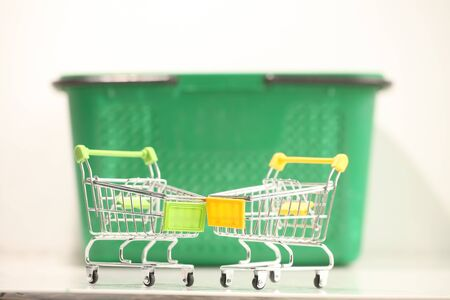 Green plastic shopping basket with black handles.