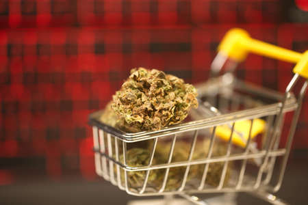 online purchase using a computer from home. cannabis in a supermarket trolley. computer keyboard