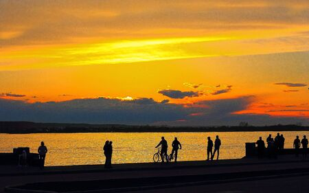 the townspeople admire the sunset on the waterfront