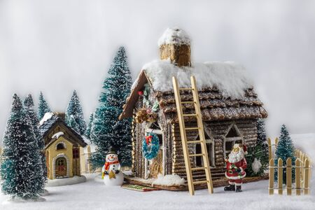 next year: New Year Christmas house decorated with snow figure Santa Claus snowman next to wooden house.