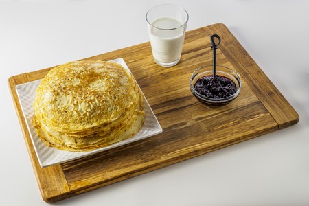 Crepes or pancakes with milk and black currant jam on wood 写真素材
