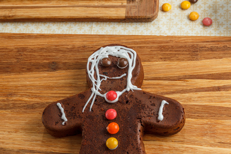 Decorated brown homemade gingerbread man for Christmas on wood Stock Photo