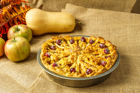Fall traditional apple pie still life with pumpkin, and apples