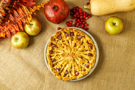 Fall traditional apple pie still life with pumpkin, cranberry and apples