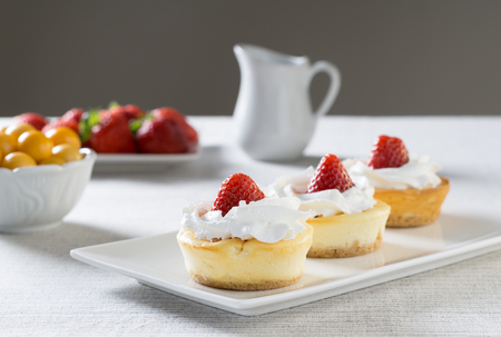 Mini cheesecakes with Strawberry and whipped cream on a plate