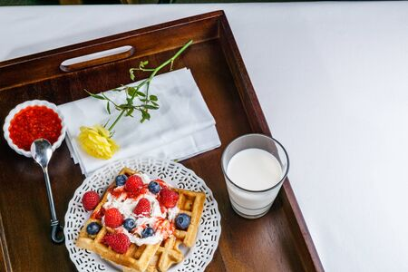 Fresh belgian waffle with berries with milk breakfast on a tray.