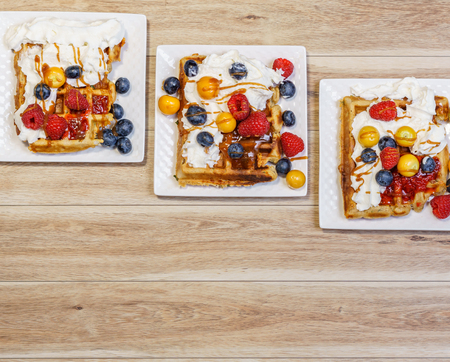 belgian waffle with raspberries and blueberries on wood table.
