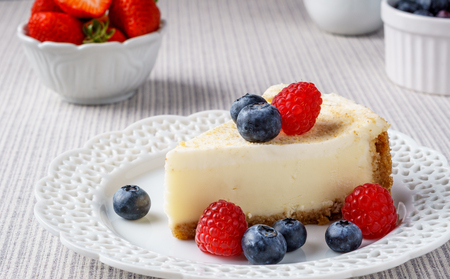 Delicious cheesecake with strawberry and blueberry on a table top view