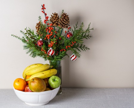 berries pine cones and fresh winter greenery as a bouquet on a white table in front of a wall, beautiful christmas decoration with fruit in thw vase 免版税图像