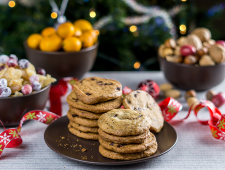 freshly baked chocolate chip cookies on a table with blurred christmas tree background 写真素材